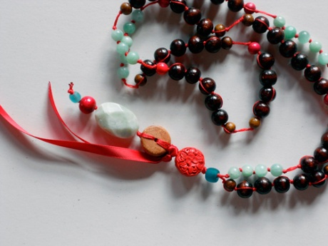 A long piece featuring dark-coloured larger wooden beads with accents of red and aqua.
