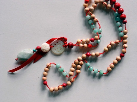 A long piece featuring light-coloured wooden beads with accents of red and aqua.