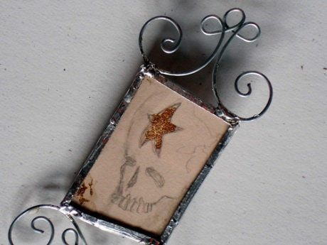 Lovely little skull and star drawing between glass and copper with wire embellishments.