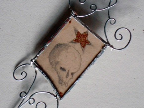 Second little skull and star drawing between glass and copper with wire embellishments.