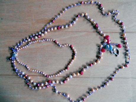 Three strands of freshwater pearls in pale pink, peach, mauve and magenta with accents of dyed magenta jade and silver cast hearts by Steve Mehle.