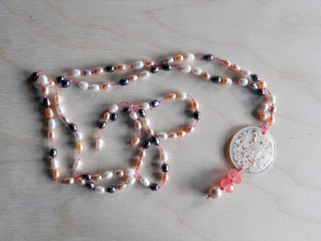Pink, peach, white and purple/grey freshwater pearls with a mother-of-pearl dragon pendant and an accent of cherry quartz.