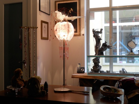 """The lights are low to capture the light cast by GJ's newest sculpture, """"Trip to the Moon,"""" a lamp and kinetic sculpture."""