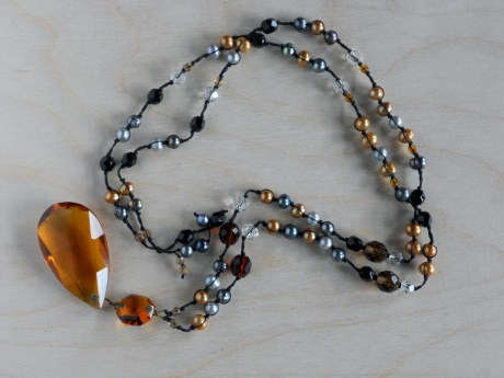 An amber-coloured chandelier crystal hanging from pearls of amber, siilver and grey colours with amber- and clear-coloured faceted glass. © Firehorse Designs