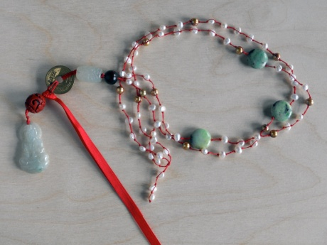 Small white pearls and green stone on red thread with coin, resin cinnabar and a pale jade Buddha. © Firehorse Designs