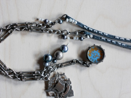 This antique watch chain with medallion and encased coin wanted to be hung as a necklace. I added a smokey-blue length of suede into which I sewed tiny seed pearls. I also added a grouping of pearls to the chain. This piece was commissioned as a gift and the recipient was very pleased. © Firehorse Designs