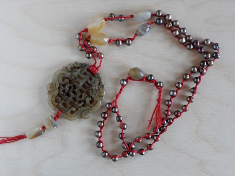 Brown pearls braided onto red threads with miscellaneous stones and a carved brown jade pendant. © Firehorse Designs 2013