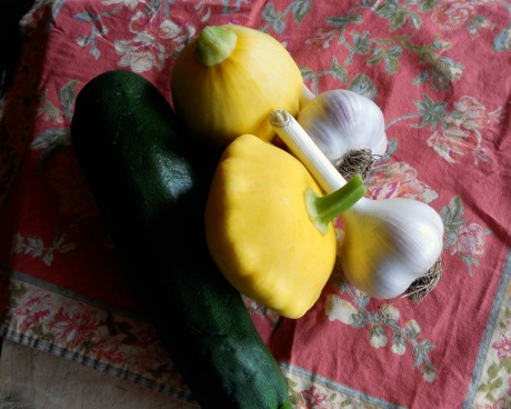 "A fresh feast of green zucchini, yellow pattypans and ""music"" variety garlic."