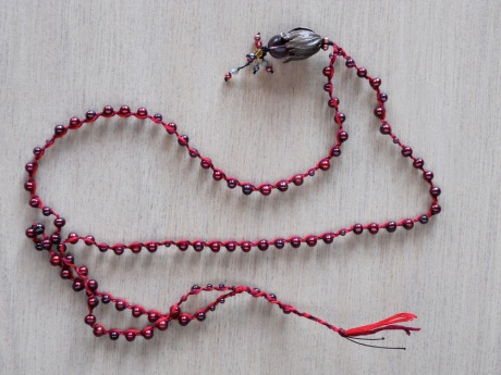 Deep red pearls and garnets are braided into dark maroon and bright red embroidery floss with a brass floral pendant.