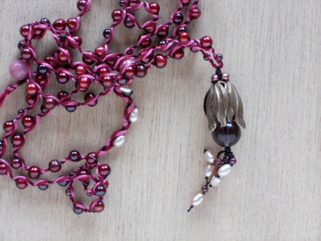 Detail. Pale pink freshwater pearls and tiny garnets are used in the floral detail.