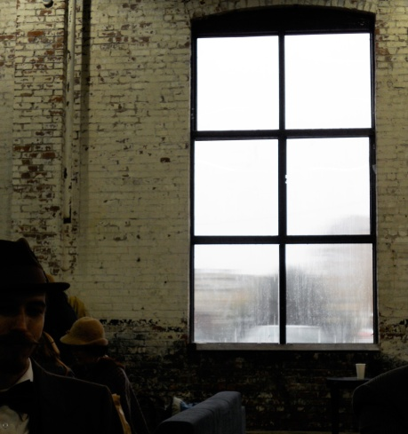 "The ""art"" shot of a rain-soaked window with our friend Riley (who won for Best Men's Facial Hair) seated on the left."