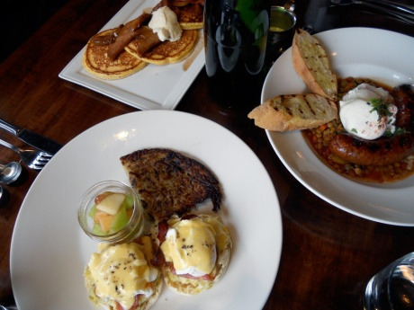 Yum! Clockwise from bottom left: The Weekend Crossword (creamed leeks and crispy prosciutto with truffled hollandaise benny), the Catalano Corn Cakes (with mascarpone cheese, caramelized apple and bacon), and the Tagine (a Moroccan vegetable stew with grilled lamb sausage).