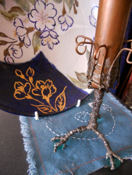 One of GJ's copper bud vases and a colourful plate rest on a small embroidered piece by Annie.