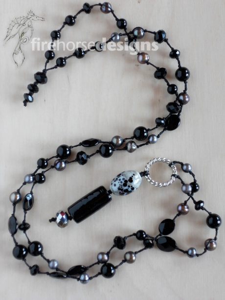 Black stones, grey pearls and glass.