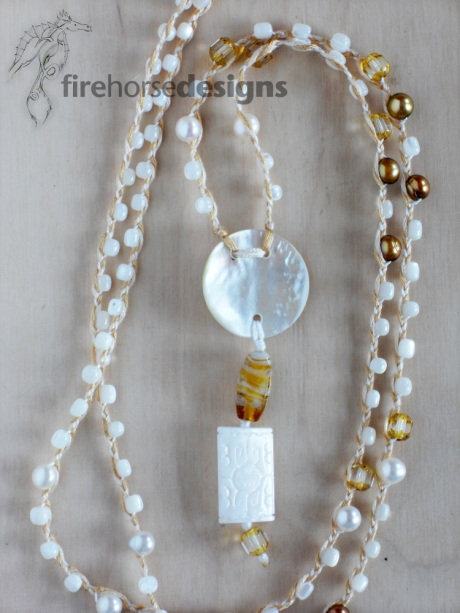 Mother of pearl, gold-coloured fresh-water pearls and glass.