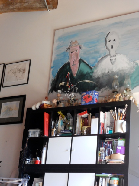 Behind GJ's workspace; new art on the left, an old piece above the cabinet, and lots of materials, books and ephemera.