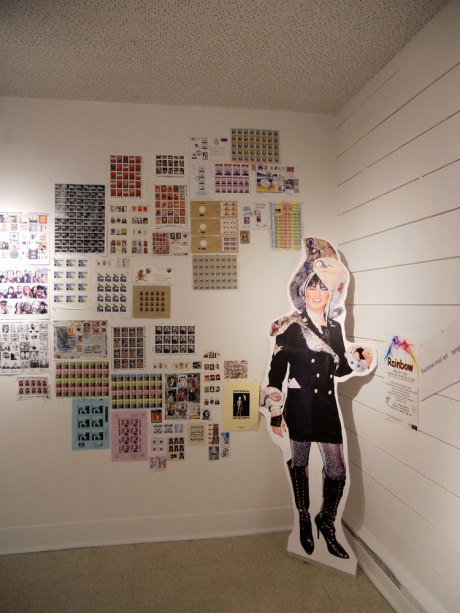 The Dame in cardboard with a wall of art stamps.